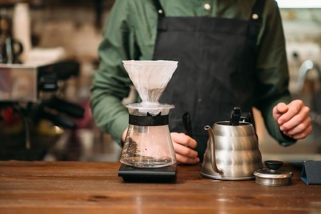 Metalen koffiepot en glas op een toog tegen ober in zwart schort.