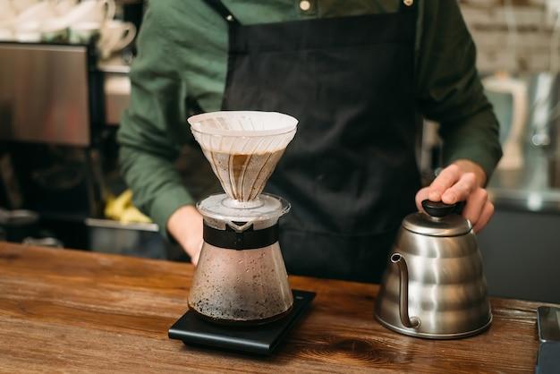 Metalen koffiepot en glas op een toog.