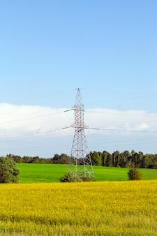 Metalen kolom voor hoogspanningslijnen tegen de achtergrond van landbouwgebieden en blauwe lucht, zomerlandschap