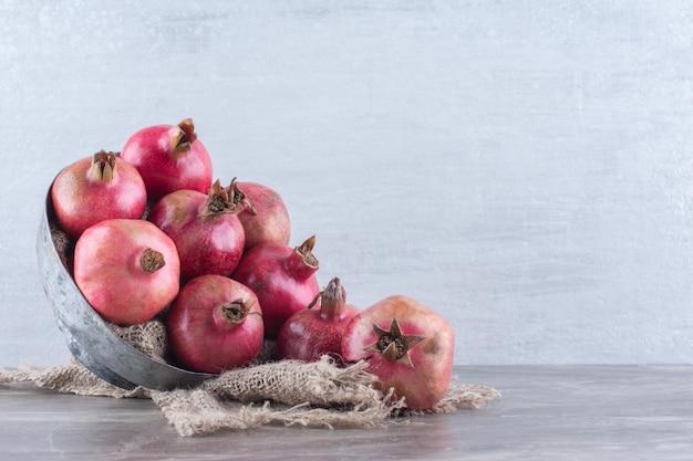 Metalen kom vol granaatappels op een stuk doek op een marmeren ondergrond