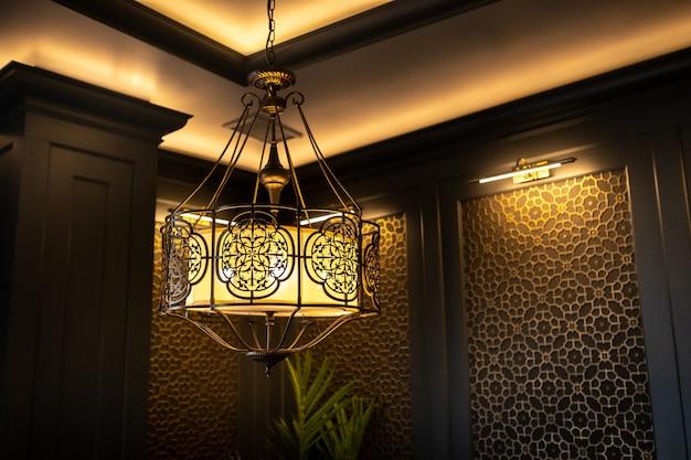 Metalen lamp in oosterse stijl aan het plafond van het interieur.