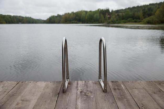 Metalen leuning voor afdaling in het meer, ijzeren ladder voor zwemmers