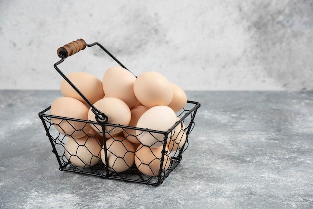 Metalen mand met verse biologische rauwe eieren op marmeren oppervlak.