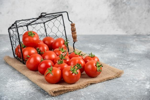 Metalen mand met verse biologische tomaten op marmer.