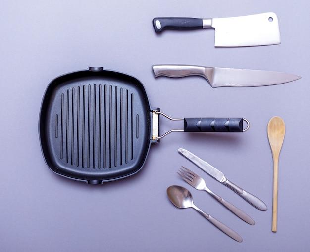Metalen messen met zwart op een grijze tafel, grillpan, handdoek. plat leggen, lay-out.