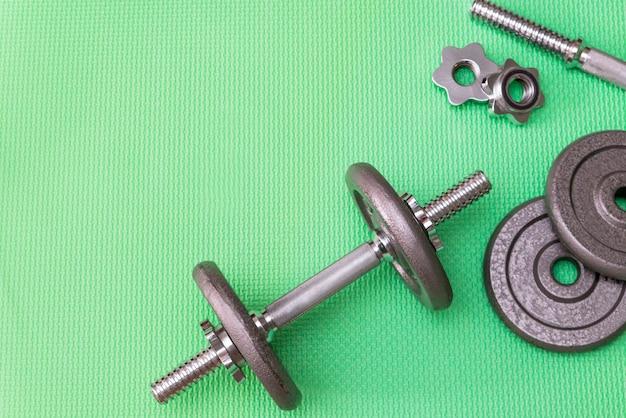 Metalen metalen halters voor sport op een groene achtergrond, grijze gewichten halters voor sport