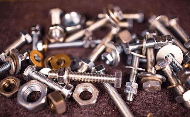 Metalen moeren en een moersleutel liggen in een chaotische volgorde op de werktafel van de monteur. reparatie- en reserveonderdelenconcept