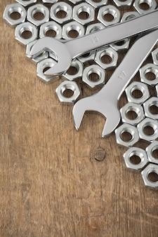 Metalen moeren en moersleutelhulpmiddel op houten muurtextuur
