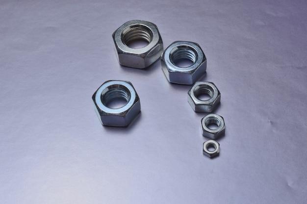Metalen moeren van verschillende groottes liggen op een metalen oppervlak. detailopname.