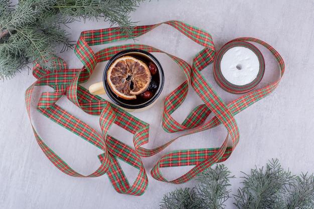 Metalen mok hete thee en feestelijke linten op witte achtergrond.