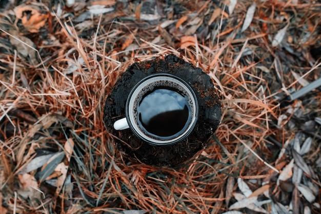 Metalen mok met een warme drank staat op een boomstronk in een herfstbos. de lucht wordt weerspiegeld in de beker
