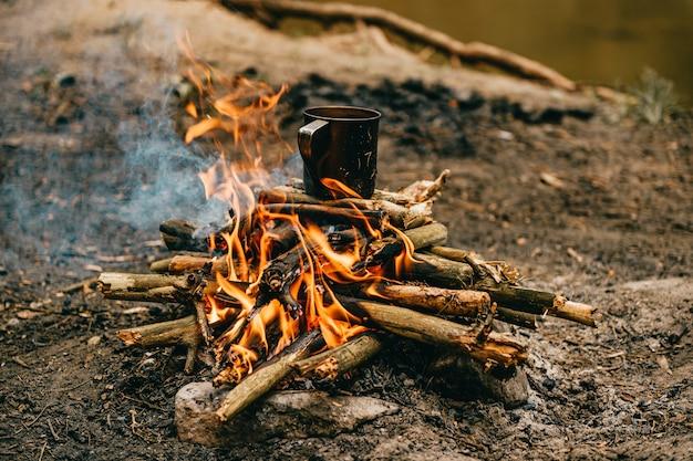 Metalen mok warmt op op vreugdevuur