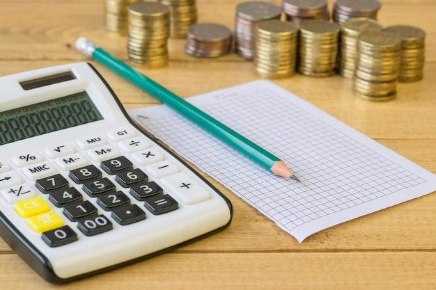 Metalen munten en rekenmachine op een houten tafel