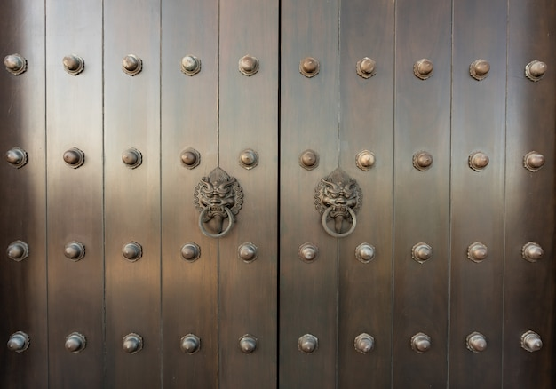 Metalen oosters leeuwengreep op teakhouten deur. antieke oosterse deurkloppers.