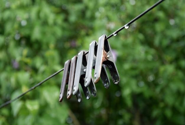 Metalen oude wasknijpers met regendruppels op de achtergrond van een natuurlijk landschap