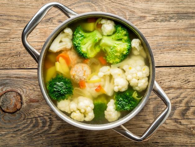 Metalen pan met heerlijke warme soep van groenten en gehaktballen, bloemkool, broccoli, wortels