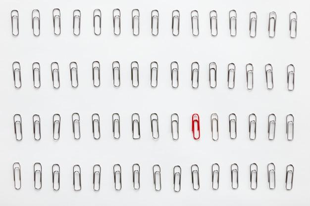 Metalen papierclips in rijen, één rood verschillend van de andere