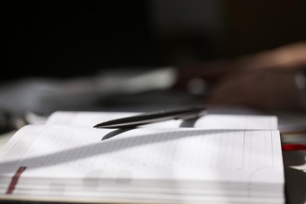 Metalen pen liggen op schaduwlijnen van notebooks