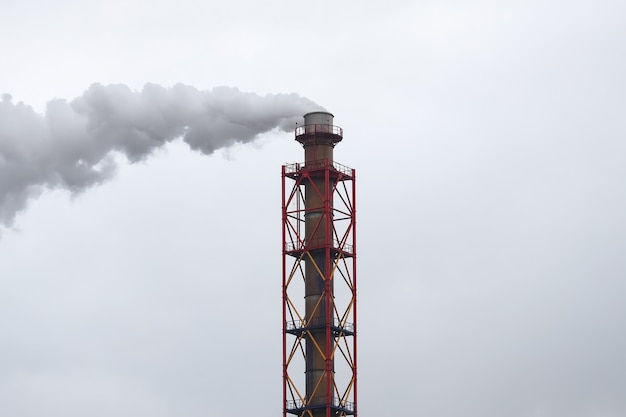 Metalen pijp waar witte rook uit komt tegen de grijze lucht