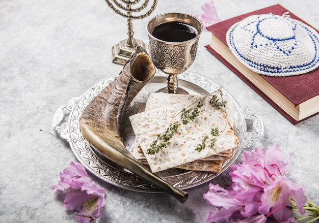 Metalen plaat met matzah kiddush cup, shofar hoorn op een lichte achtergrond gepresenteerd als een pesach feest of maaltijd met kopie ruimte. joodse traditionele objecten, keppeltje, tallit, gebedenboek