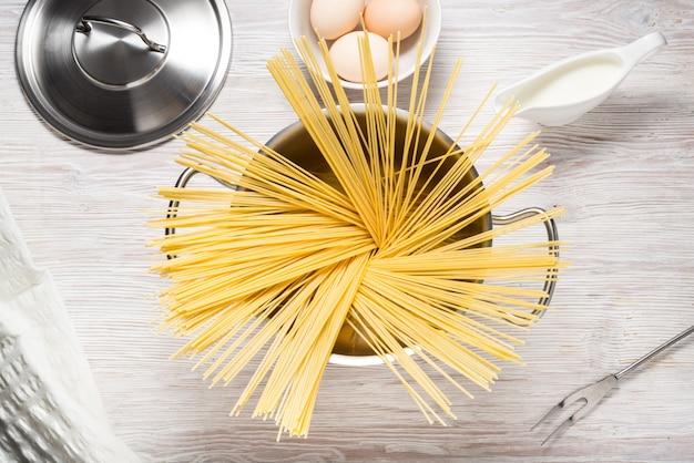 Metalen pot kookgerei, fornuis met pasta op keukentafel
