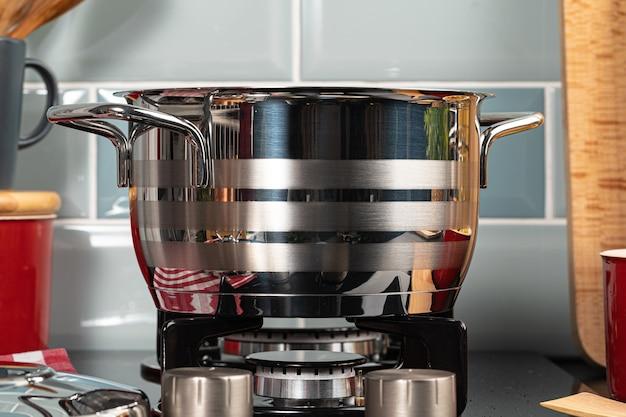Metalen pot op een gasfornuis-brander thuis keuken close-up