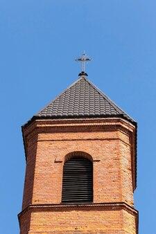 Metalen religieus kruis op de oude toren van rode baksteen en het dak van de kerk, tegen de achtergrond van de blauwe lucht het bouwelement