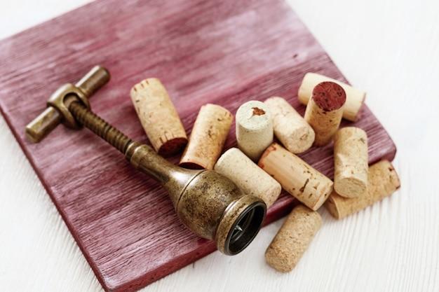 Metalen retro kurkentrekker en heap gebruikte wijnkurken op houten tafel.