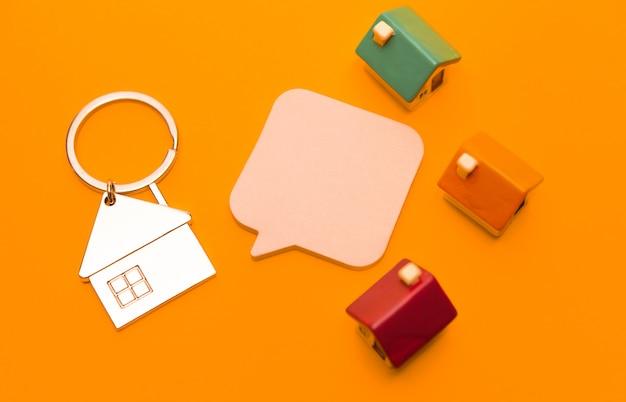 Metalen sleutelhanger in de vorm van een huis en speelgoedhuisjes op een oranje achtergrond