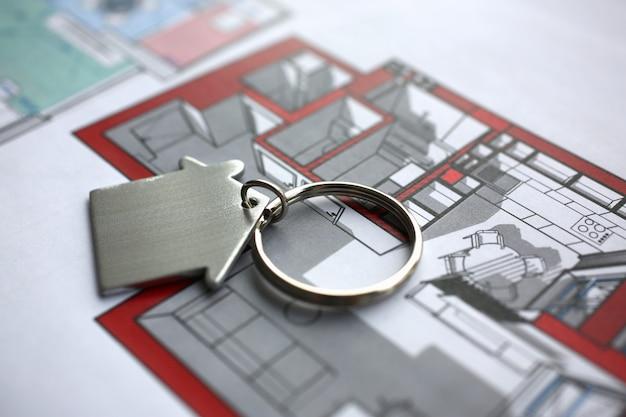 Metalen sleutelhanger in vorm miniatuur huis ligt