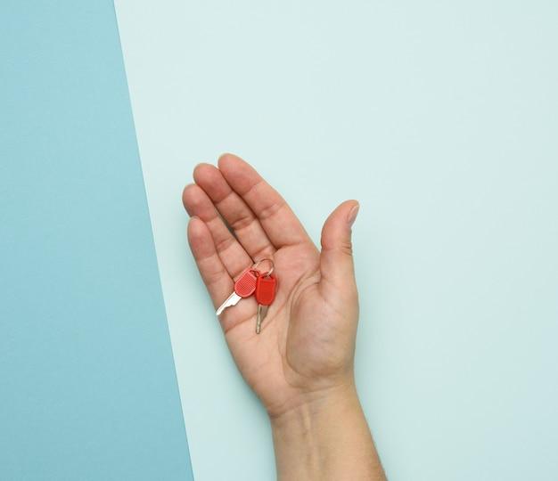 Metalen sleutels in vrouwelijke handen op een blauw
