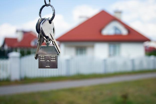 Metalen sleutels van een nieuw huis op woongebouwen.