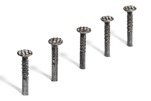Metalen spijkers gehamerd in een wit oppervlak