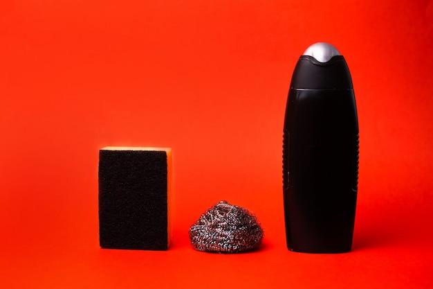 Metalen spons en spons om te wassen met het product in een zwarte fles