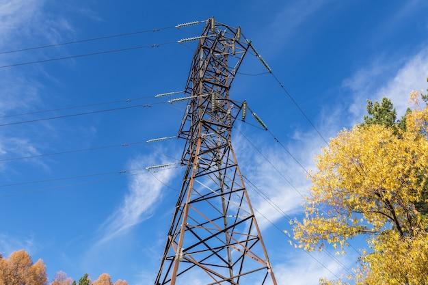 Metalen steun van een hoogspanningslijn met draden en isolatoren tegen een blauwe hemel met wolken