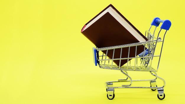 Metalen supermarktwagen met dik boek en kopieerruimte