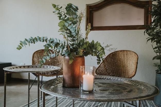 Metalen tafel met rieten stoelen, houten vazen, tapijt en spiegel