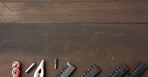 Metalen tang en verschillende spuitmonden op een bruin houten ruimte