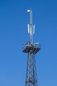 Metalen toren met antennes voor communicatie met mobiele telefoons tegen blauwe lucht