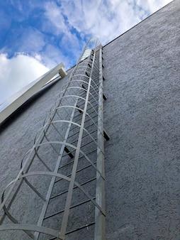 Metalen trap (trap) aan de buitenkant van een modern gebouw. ladder die tot blauwe hemel leidt