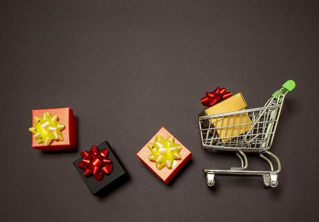 Metalen trolley met een geschenkdoos op een zwarte achtergrond met lege ruimte voor tekst.