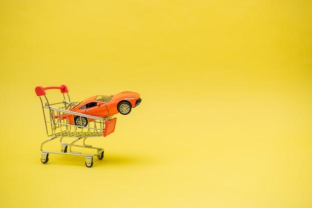 Metalen trolley met een oranje auto op een gele geïsoleerde achtergrond met ruimte voor tekst