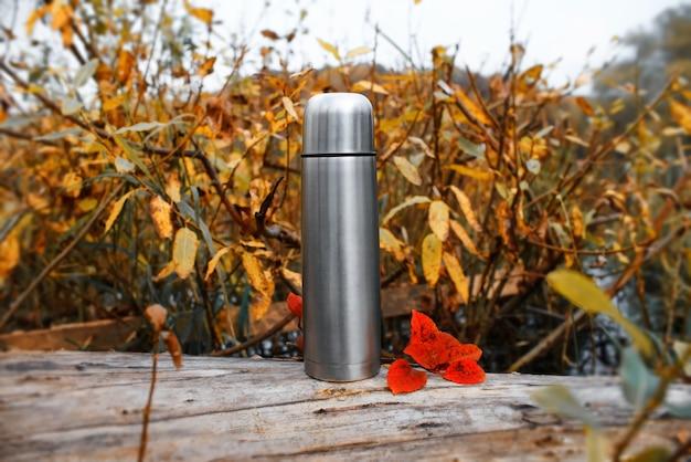 Metalen vacuüm thermoskan in het herfstbos.