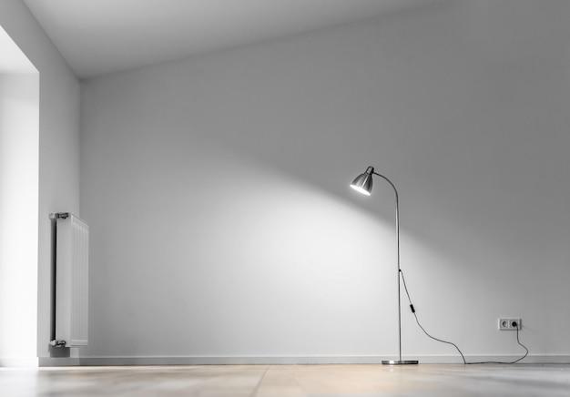 Metalen vloerlamp in lege ruimte met schaduw op witte muur, kopie ruimte voor tekst
