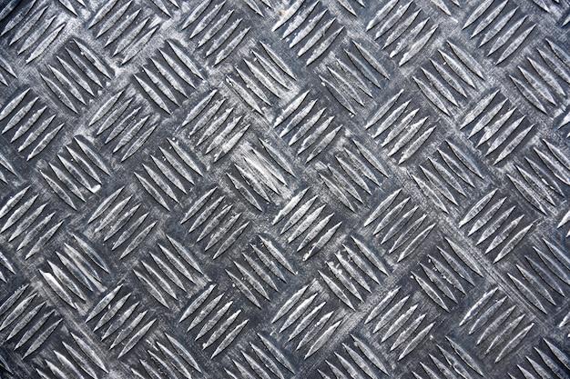 Metalen vloerplaat met ruitpatroon, ijzeren textuur.