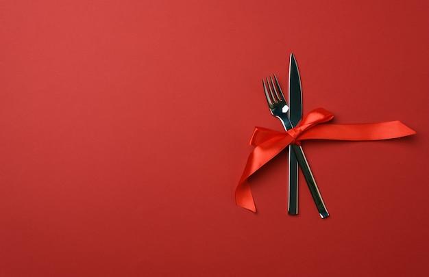 Metalen vork en mes vastgebonden met een rood zijden lint