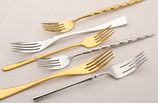 Metalen vorken op een licht tafellaken. gouden en zilveren set vorken op een roze achtergrond