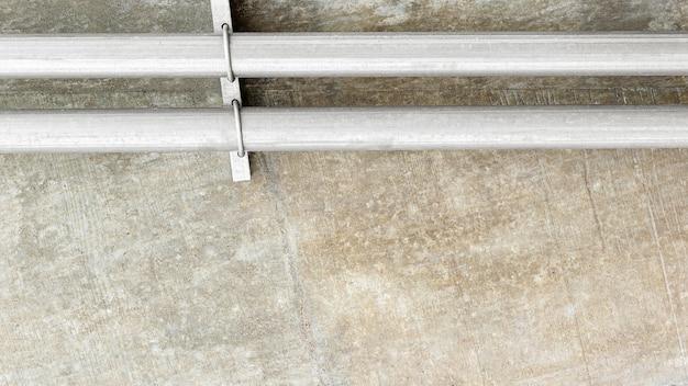 Metalen waterleidingsysteem wordt geïnstalleerd op de betonnen muur.