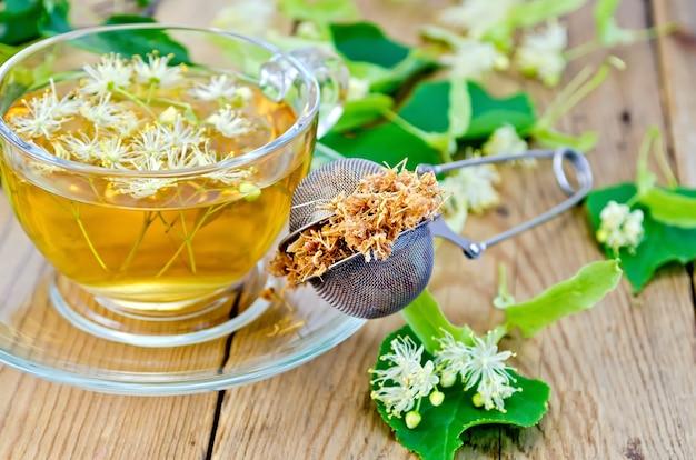 Metalen zeef met gedroogde bloemen van limoen, verse bloemen linde, thee in glazen beker op de houten planken