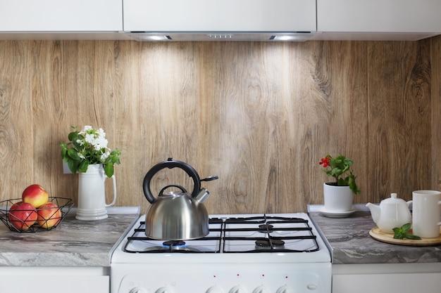 Metalen zilveren ketel op gasfornuis en theepot met kop in keuken